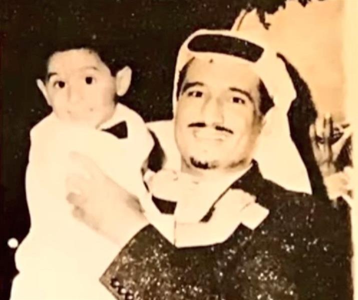 صورة قديمة في الستينيات للملك سلمان وهو يحمل ابنه الأمير أحمد
