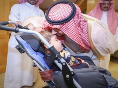 في موقف أبوي.. نائب أمير الجوف يحمل طفلة معاقة لمشاهدة حكام المملكة (صور)